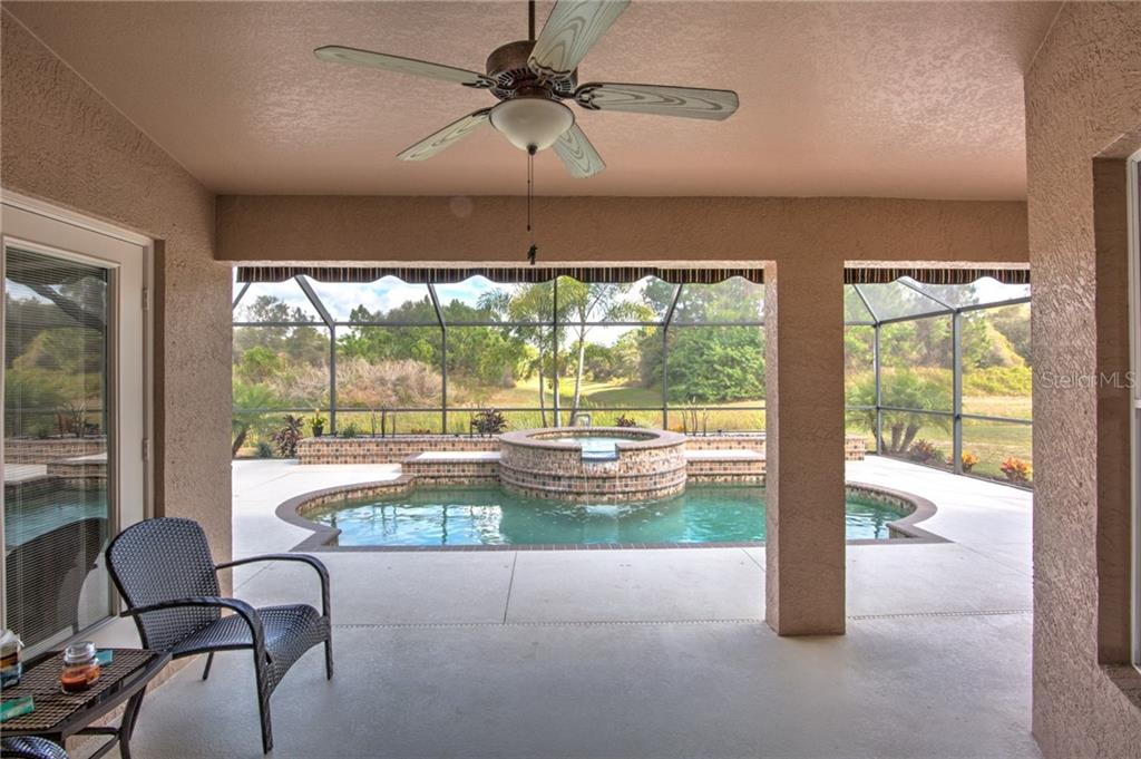 Well-appointed pool, spa, and waterfall. Note:  Exterior door int he middle of the picture to bathroom - Single Family Home for sale at 6612 Deer Run Rd, North Port, FL 34291 - MLS Number is N6103231
