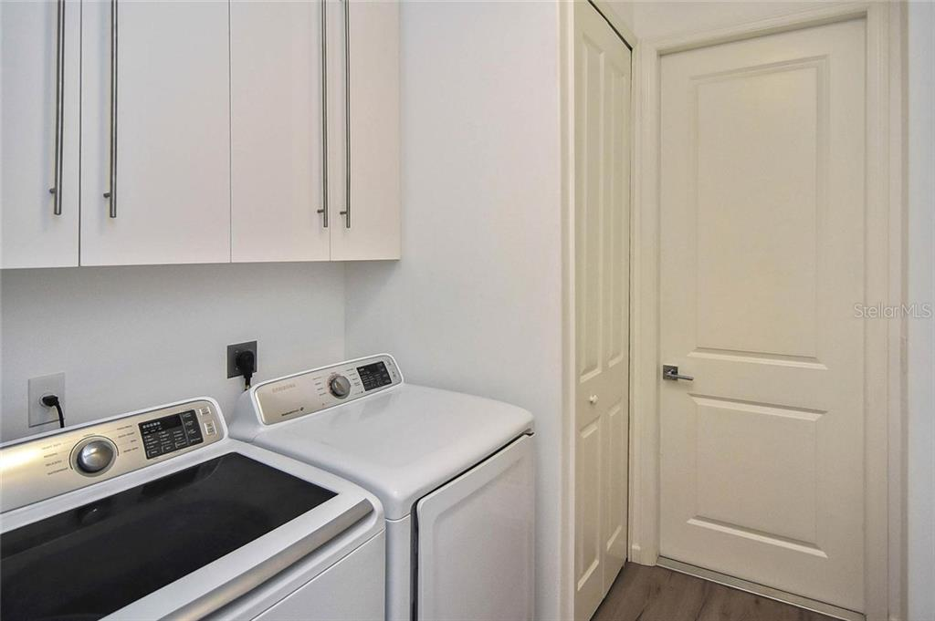 Laundry with storage cabinets - door goes to garage - Single Family Home for sale at 624 Lehigh Rd, Venice, FL 34293 - MLS Number is N6105257