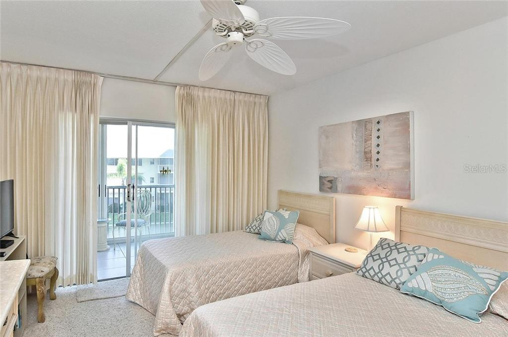 Guest bedroom with sliders to  lanai - Condo for sale at 1150 Tarpon Center Dr #303, Venice, FL 34285 - MLS Number is N6110126