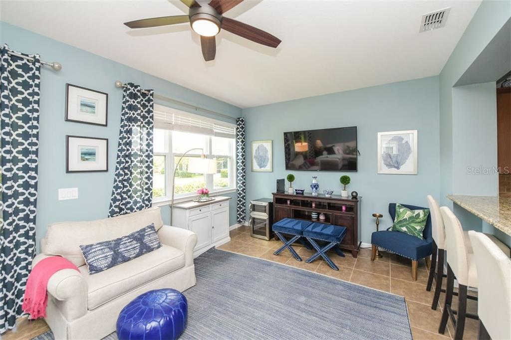 Great room featuring tile floors and view of the pond.   Open to kitchen. - Townhouse for sale at 12236 Trailhead Dr, Bradenton, FL 34211 - MLS Number is N6111119