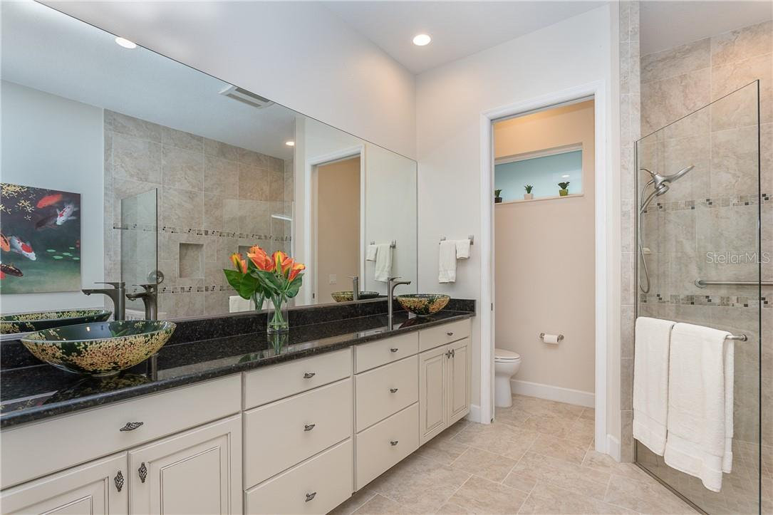 Spacious owner's bath with vessel sinks, plenty of storage & walk-in shower. - Single Family Home for sale at 1670 Maria St, Englewood, FL 34223 - MLS Number is N6113779