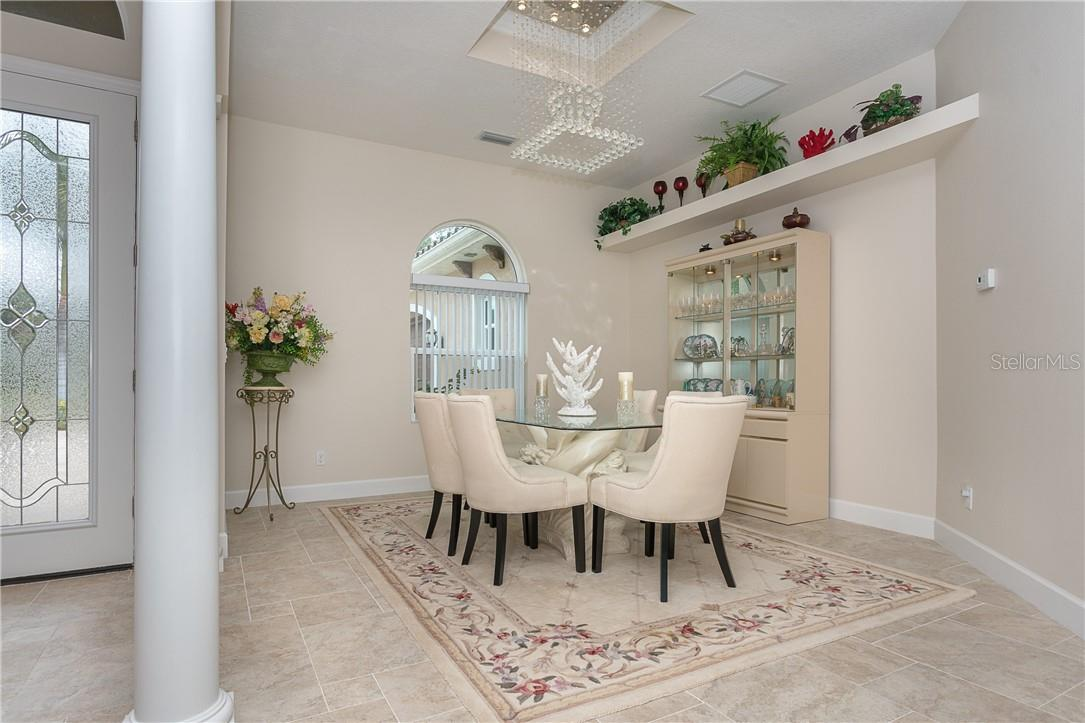 Formal dining enhanced by LED crystal chandelier. - Single Family Home for sale at 1670 Maria St, Englewood, FL 34223 - MLS Number is N6113779