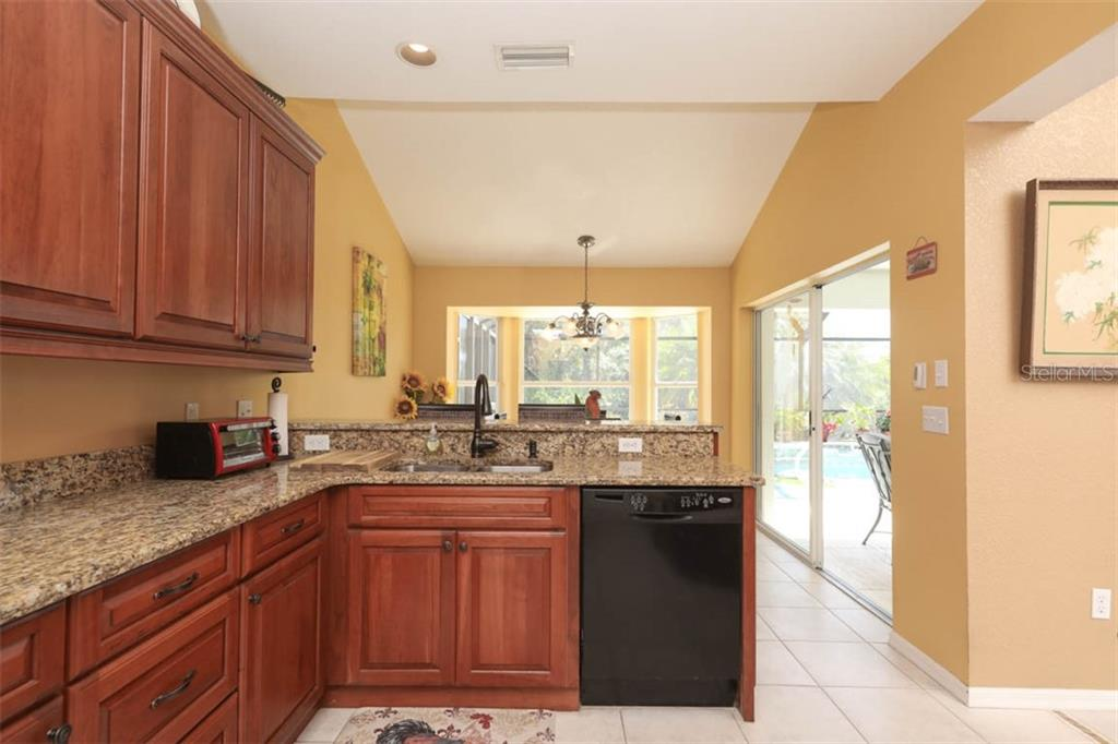 Beyond the raised breakfast/entertaining bar you will find a bright and cheerful eat-in area that offers views out to the pool.  Directly behind us is a full size closet pantry. - Single Family Home for sale at 24620 Dolphin Cove Dr, Punta Gorda, FL 33955 - MLS Number is C7413467