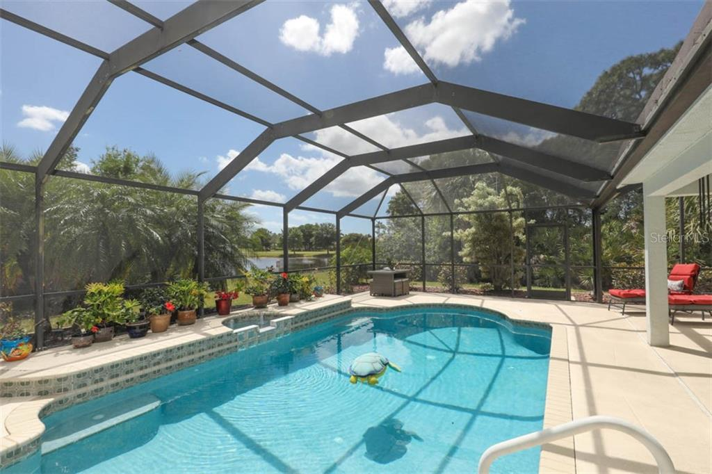 Sparkling heated pool with pond and golf course views, along with an abundance of privacy, awaits you. - Single Family Home for sale at 24620 Dolphin Cove Dr, Punta Gorda, FL 33955 - MLS Number is C7413467
