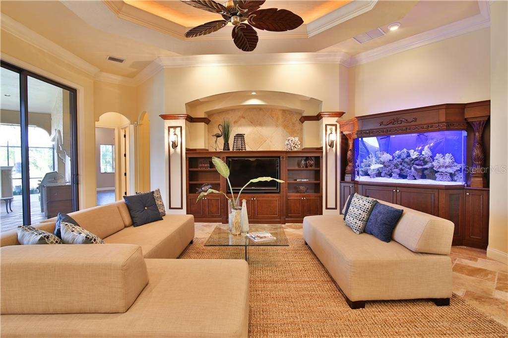 Family room with built-in entertainment shelving; a salt water aquarium.  This open floor plan is adjacent to the kitchen and breakfast room. - Single Family Home for sale at 8365 Catamaran Cir, Lakewood Ranch, FL 34202 - MLS Number is A4187448