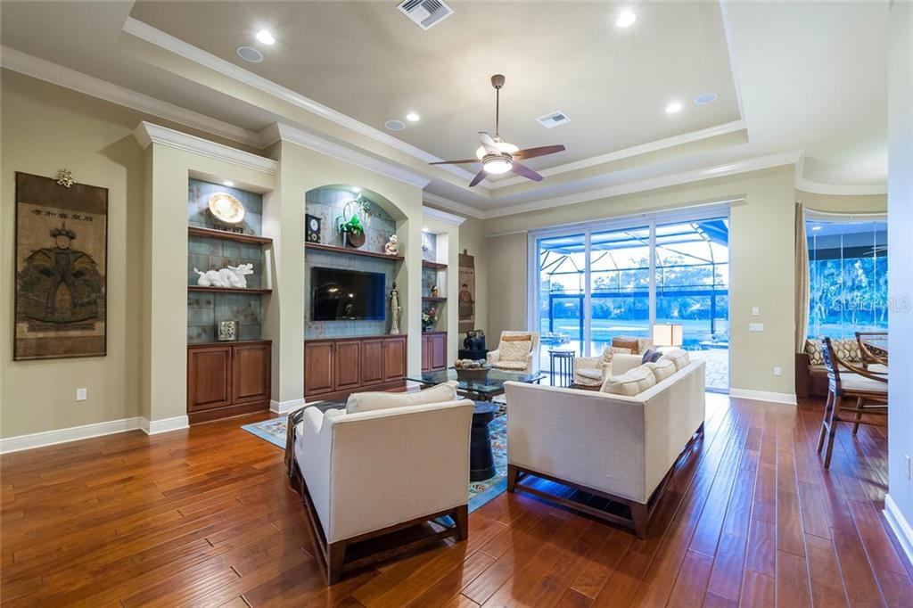 Wood floors, functional built-ins, and stepped ceilings allow light and that gorgeous view to the outside.  Impact glass all around house provides peace of mind. - Single Family Home for sale at 12312 Newcastle Pl, Lakewood Ranch, FL 34202 - MLS Number is A4403090
