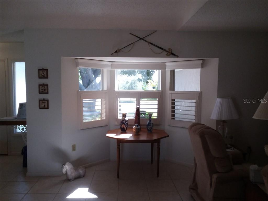 Bay window with plantation shutters in living room. - Single Family Home for sale at 3176 E Village Dr, Venice, FL 34293 - MLS Number is A4417064