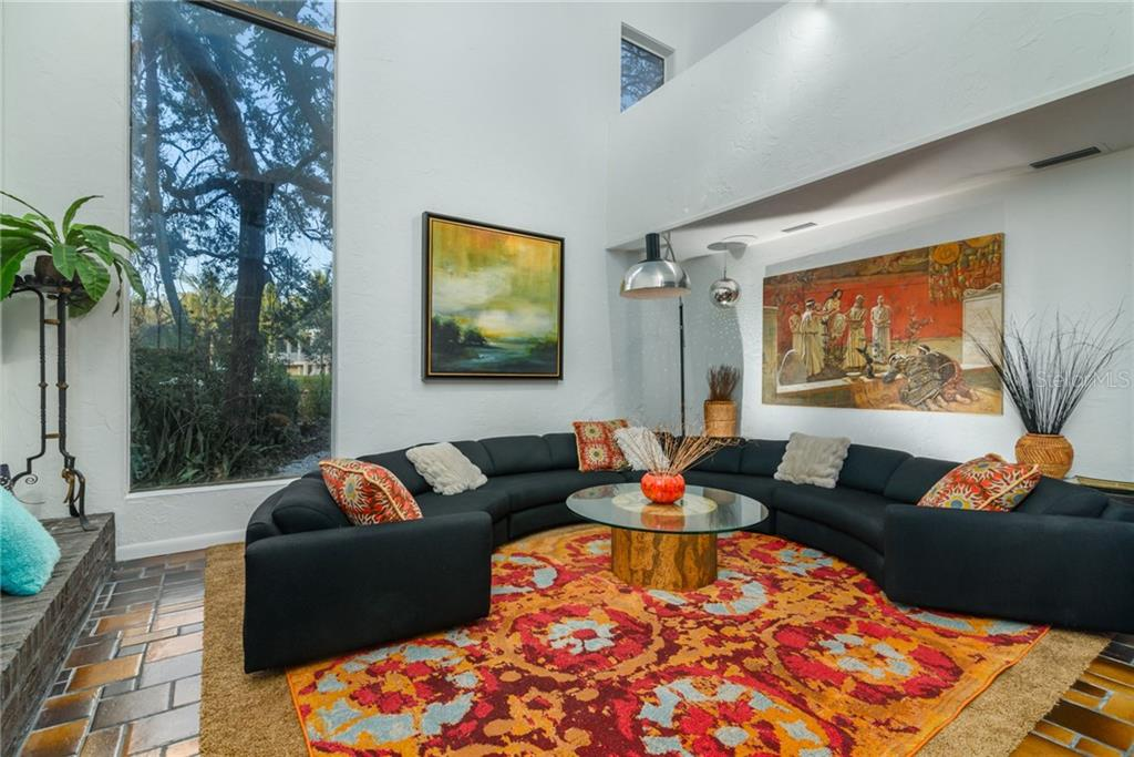 Great room with  Vaulted Ceilings and Wood Burning Fireplace with wood storage box with outside access and Vaulted Ceilings - 21' x 17' - Single Family Home for sale at 5303 Hidden Harbor Rd, Sarasota, FL 34242 - MLS Number is A4421223