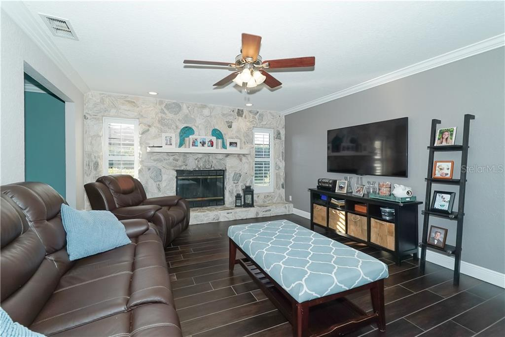 Living room with wood fireplace and office/den attached. - Single Family Home for sale at 8106 Timber Lake Ln, Sarasota, FL 34243 - MLS Number is A4423770
