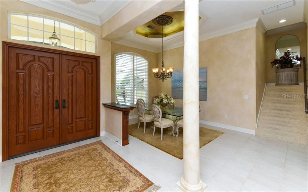 8ft. Mahogany carved doors,  formal dining room with a Tres Faux Painted ceiling and Plantation Shutters - Single Family Home for sale at 561 Ketch Ln, Longboat Key, FL 34228 - MLS Number is A4426280