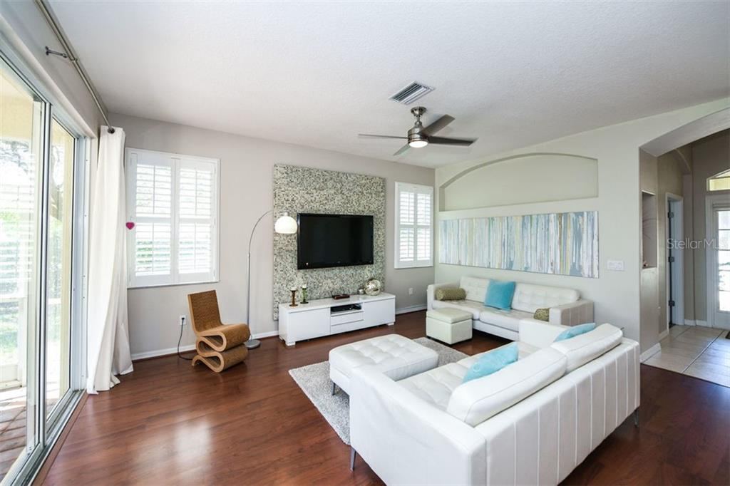 Spacious great room floor plan. Laminate flooring, plantation shutters. Wall feature with TV to convey. - Single Family Home for sale at 702 Anna Hope Ln, Osprey, FL 34229 - MLS Number is A4427993