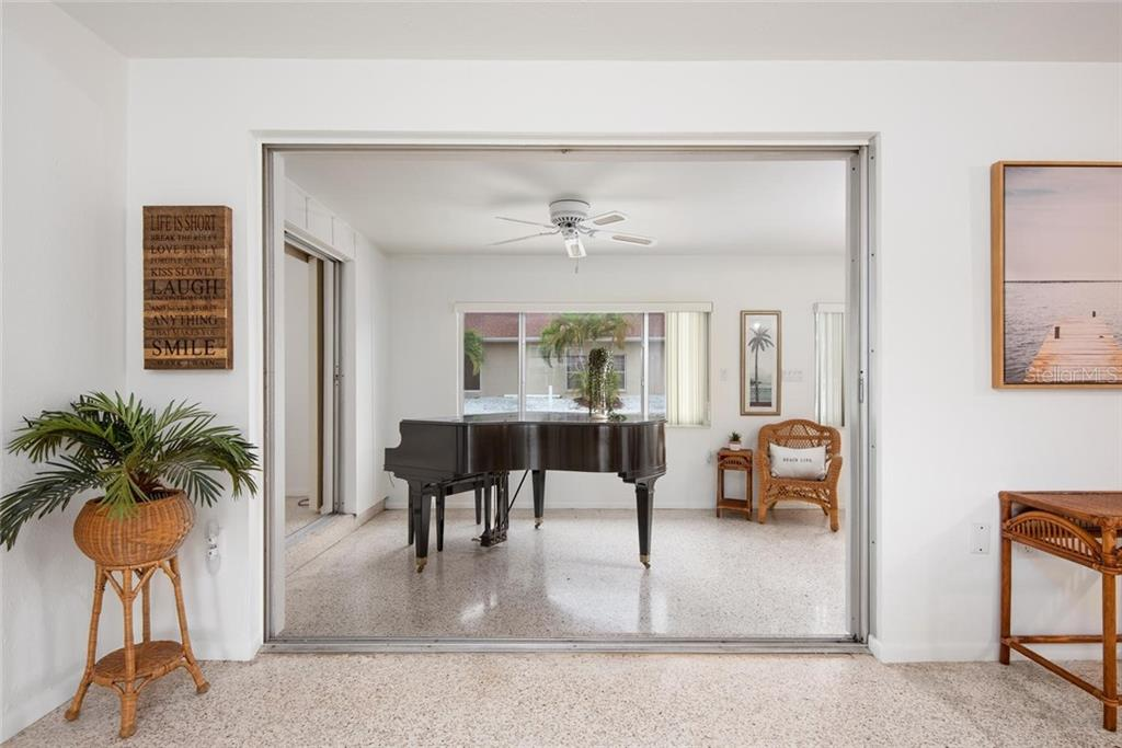 From the living area into the Florida room and out to the canal beyond. - Single Family Home for sale at 691 Tarawitt Dr, Longboat Key, FL 34228 - MLS Number is A4451584